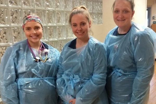 Essential workers wear plastic medical gowns